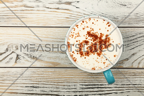 Close up blue cup full of latte cappuccino coffee with CAFE word shaped chocolate on milk froth over background of white vintage wooden planks table, close up, elevated top view, directly above