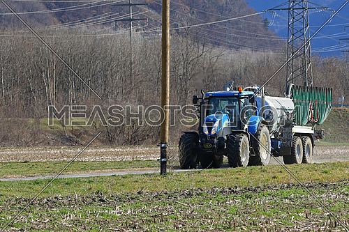 Agricultural tractor pulling a trailer on a farm road