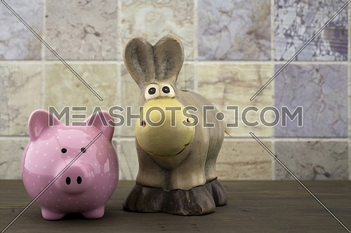 Cute little piggy bank and toy donkey close up front view against a tiled background