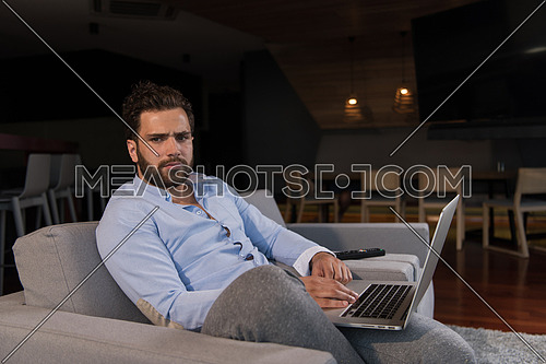 technology, home and lifestyle concept  of man working from home using laptop computer and sitting on sofa