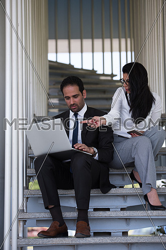 Business executives conducting business while sitting on steps in a corporate office using laptop,tablet and mobile phones