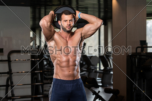 Young Man Exercising Abdominal Muscles With Weights In A Modern Fitness Club
