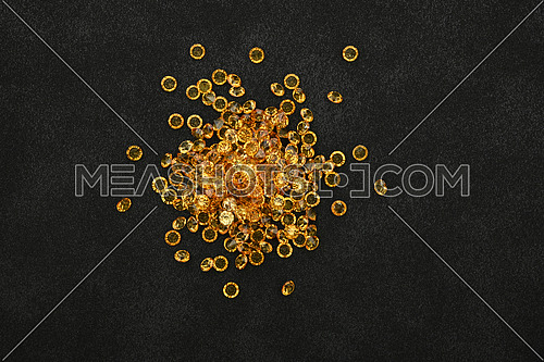 Close up heap of golden yellow rhinestone crystals over black leather background, elevated top view, directly above