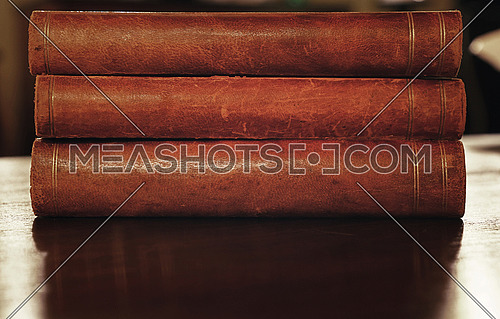 Stack of three old vintage brown leather hardcover books on table