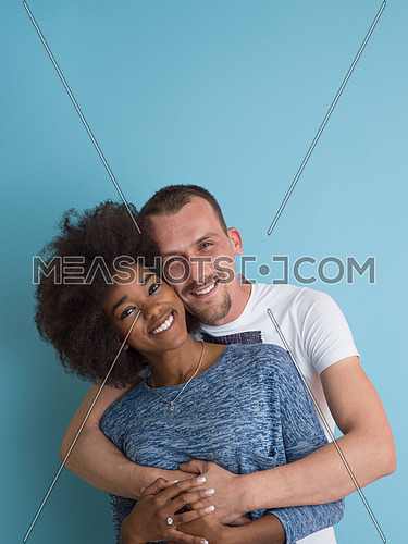 Young happy multiethnic couple laughing and hugging isolated on a blue background