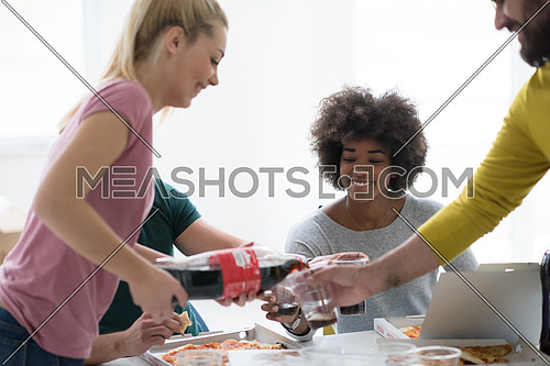 multiethnic group of young people have a lunch break after moving to a new home