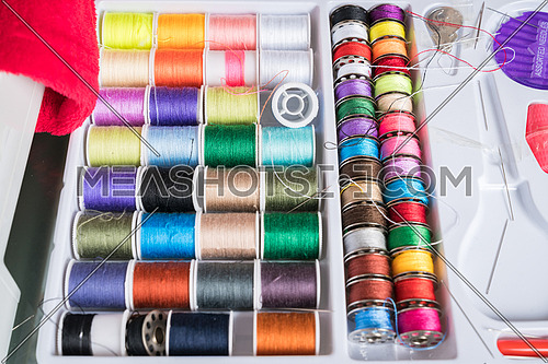White plastic box inside Sewing kit with colored spools of threads and needles