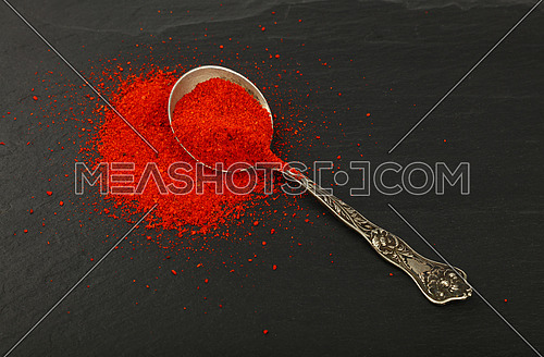 Close up one vintage antique metal spoon full of red chili pepper or paprika powder on background of black slate board, high angle view