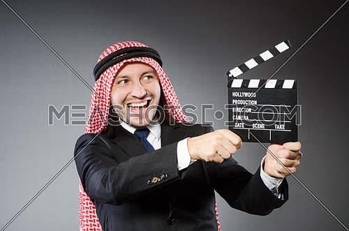 Arab man with movie clapper against grey background