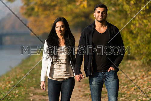 Couple Walking In Forest Through The Woods Outside During Autumn