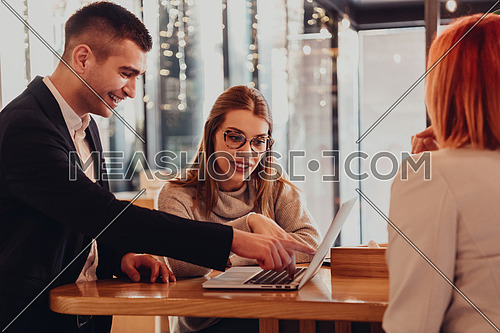 Group of friends hanging out in a coffee shop with a laptop amongst them. Happy young people sitting at restaurants using a laptop
