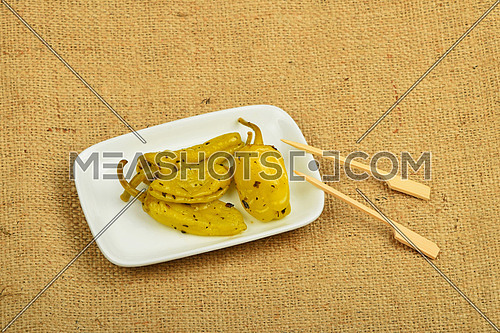 Mediterranean snack of four pickled green pepper in white plate with two skewers on burlap jute canvas