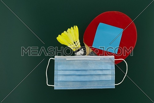 Table tennis racket and shuttlecock cover with a medical face mask. Sports during the quarantine period concept with free copy space