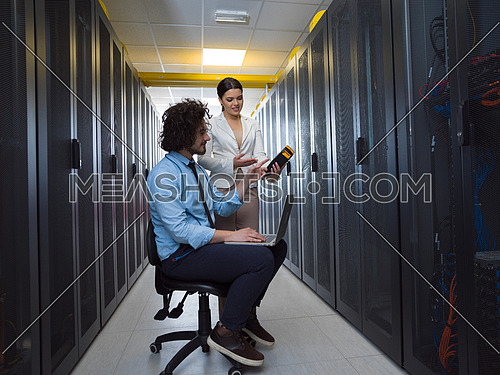 Team of young technicians working together on servers at the data center using laptop computer