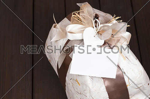 In the picture a gift bag with copy space on the wooden background.