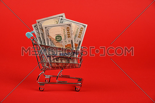 Close up several one hundred US dollar paper currency banknotes in small shopping cart over red background, low angle side view
