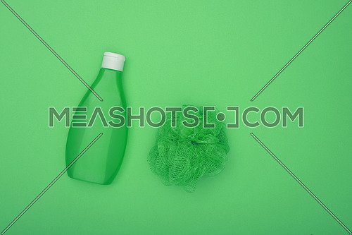 Close up one bottle of shower gel and feminine soft bath skin scrub puff over green background, elevated top view, directly above