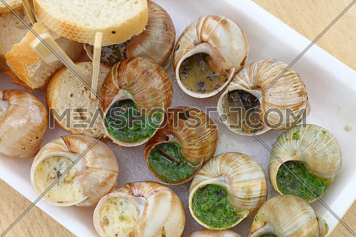 Close up street fast food take away portion of cooked escargot snails with French herbs and garlic butter and baguette bread, elevated top view, directly above