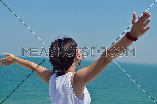 Happy  young woman with spreading arms, blue sky with clouds in background  - copyspace