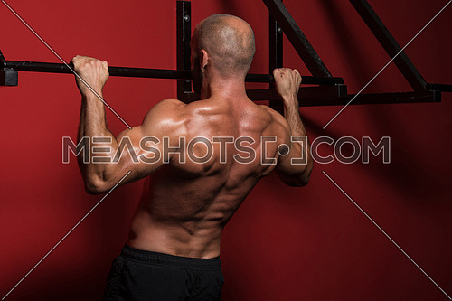 Adult Man Athlete Doing Pull Ups - Chin-Ups In The Gym