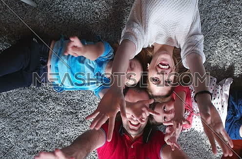 top view of  happy family lying on floor with heads together