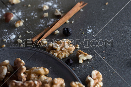 Walnuts in a metal tray with hazel nuts, raisin and cinnamon sticks