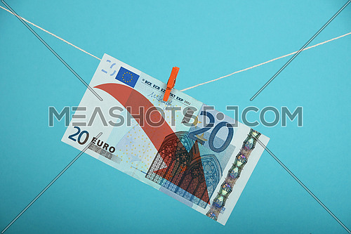 European economy crisis, decline of Euro, twenty Euro banknote with red arrow down hanged descending with pin at rope over blue background
