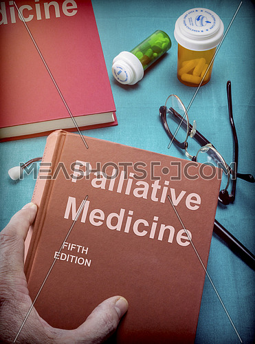 Doctor supports a book of palliative medicine in a medical laboratory