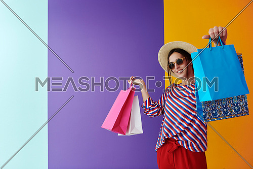 Young woman with shopping bags on colorful background. Happy girl posing with new purchases after a day of big sale. Black Friday concept