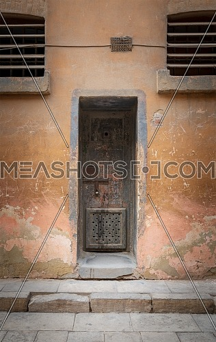 Closed rusted iron cell door and weathered grunge stone wall in closed abandoned prison at Cairo Citadel, Egypt