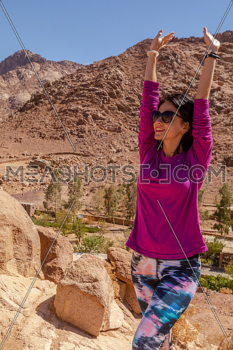long shot for a female tourist standing upon a rock explore Sinai Mountain for wadi Freij at day.