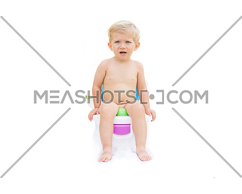 Infant boy, white caucasian serious and sitting on the potty with white background.