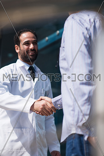 Smiling middle eastern doctor at the clinic giving an handshake to his patient, healthcare and professionalism concept