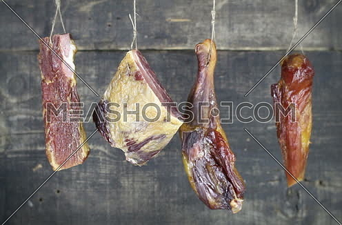 Smoked Meat Hanging And Swaying Against Wooden Background