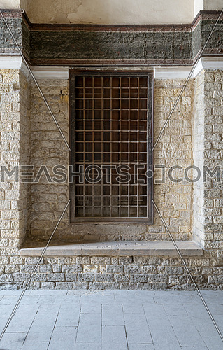 Recessed wooden window with decorated iron grid over stone bricks wall, Medieval Cairo, Egypt