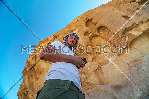 Low angel for Male Tourist wearing bedouin headscarf at Makhroum Mountain by day