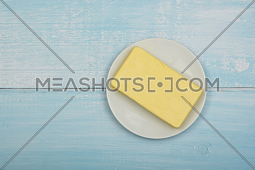 Close up open fresh yellow hard stick butter in white plate on blue rustick table surface, elevated top view, directly above