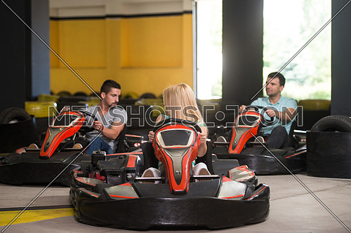 Group Of People Is Driving Go-Kart Car With Speed In A Playground Racing Track - Go Kart Is A Popular Leisure Motor Sports
