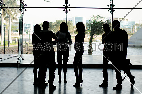 group of people standing while two men passing by in suites