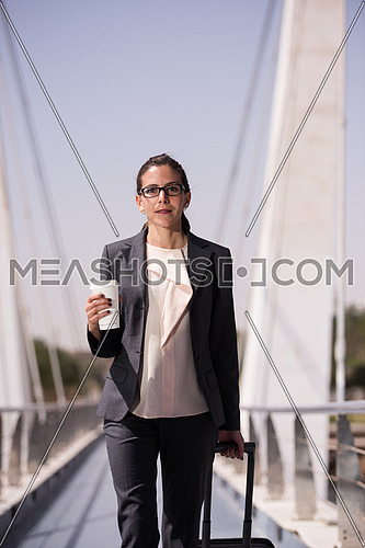 young businesswoman with travel bag and fresh morning coffee walking to catch the plain at  airport