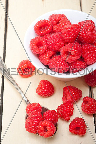 bunch of fresh raspberry on a bowl and white wood rustic  table