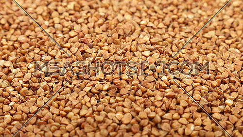 Dried brown buckwheat (Fagopyrum esculentum) groats close up pattern background, low angle view, selective focus
