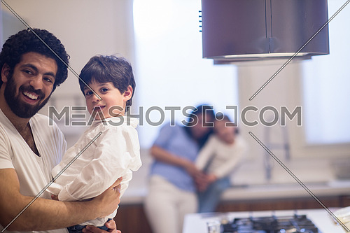 young middle east father and mother with children spend cheerful time in the kitchen