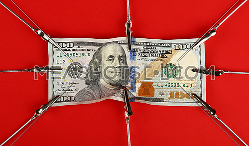 Close up one hundred US dollar paper currency banknote pulled and stretched over red background with copy space, high angle view
