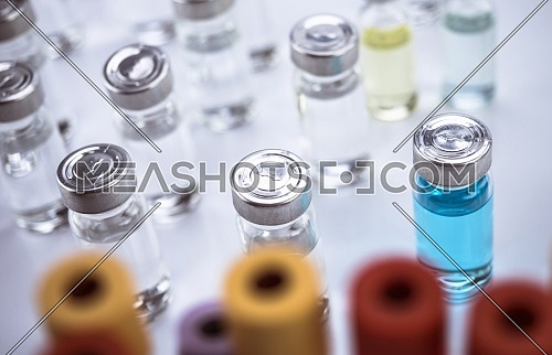 Medication vials along with blood samples in a hospital, conceptual image