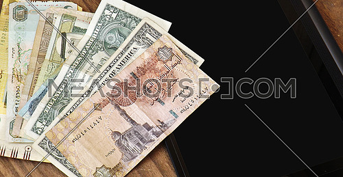 1 doller and 1 egyptian pound on wood background and tablet
