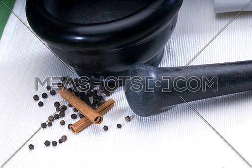 black stone mortar and pestel with cinnamon and pepper
