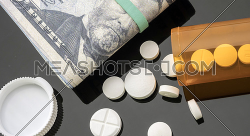 Boat of white pills along with tickets of dollar, concept of sanitary copayment