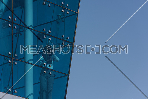 Outdoor shoot showing a female executive talking on the phone and holding tablet through the glass front of a corporate offices building with a background of blue sky