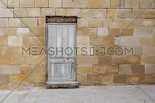 Facade of old abandoned stone bricks wall with broken weathered wooden door